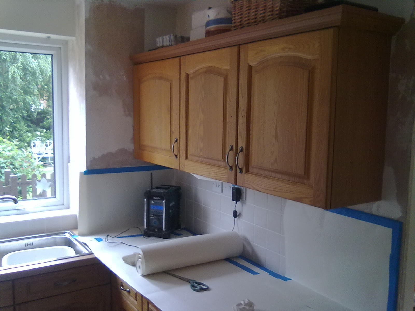 masking up wooden kitchen for painting