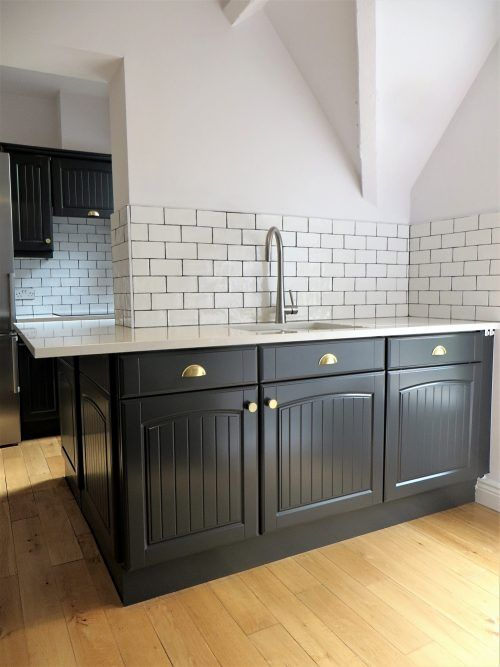 The deep charcoal cupboards of this hand painted kitchen in Ilkley with the new tiles and light white granite work top