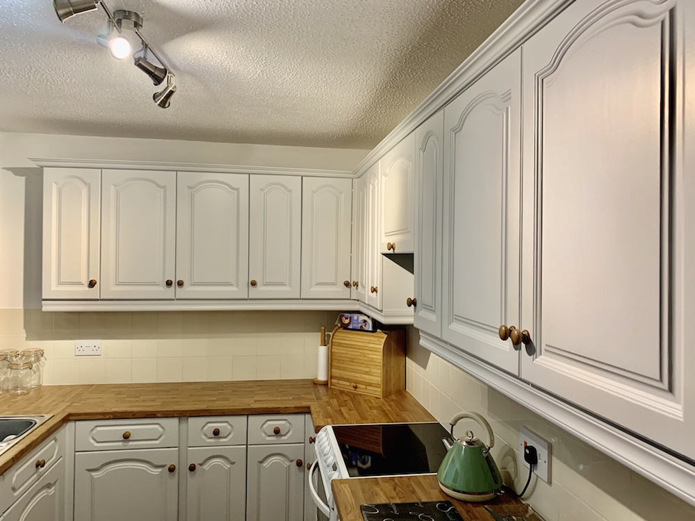 oiled oak knobs complement oak worktops in painted pine kitchen